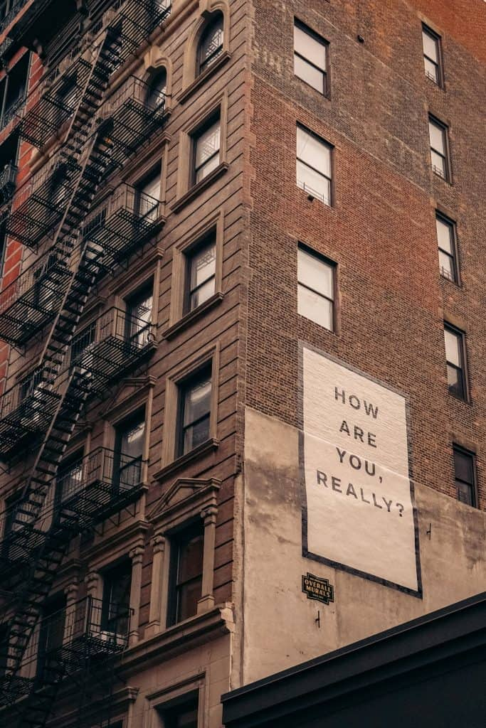 """Image of the side of a apartment building like in new york with a sign that reads, """"how are you really?"""" S4 E20 - Struggle Engaging? You Might Be Languishing Or Dormant"""