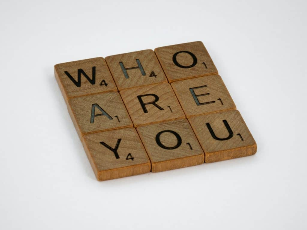 """Pictured are scrabble block letters in shape of a square 3 by 3 that reads """"Who are you"""". Today's episode is 5 Leadership Principles: Conversation with Paul Hanson, President of Epcon Franchising"""